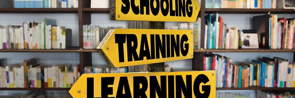 Drei Schilder mit Schooling, Training und Learning vor Bücherregal
