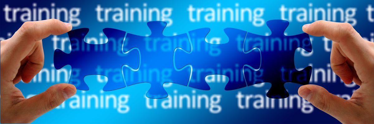 Zwei Hände sortieren Puzzleteile vor blauem Hintergrund mit dem Wort training